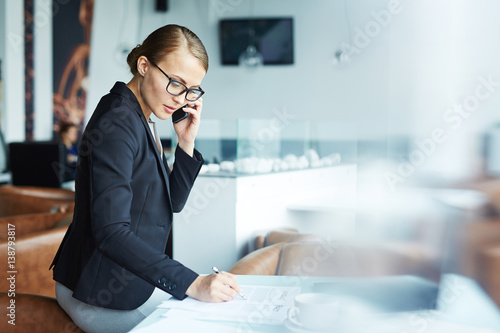 Blond confident businesswoman going over details of contract talking with partner on phone during her coffee break in modern light lounge area