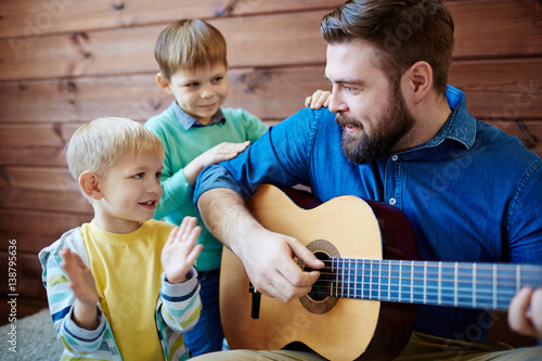 Láminas  Bearded nursery teacher giving music lesson to little boys: he playing guitar an