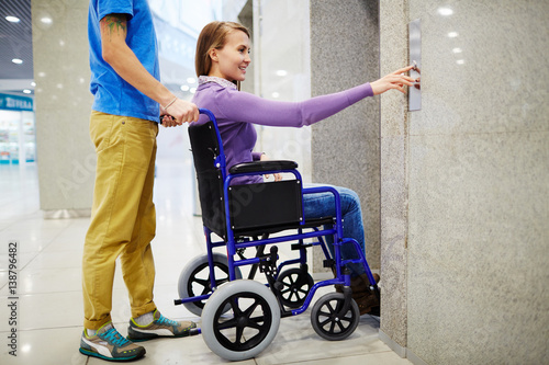 Foto  Assistant and handicapped young woman in wheelchair waiting for elevator, she pr