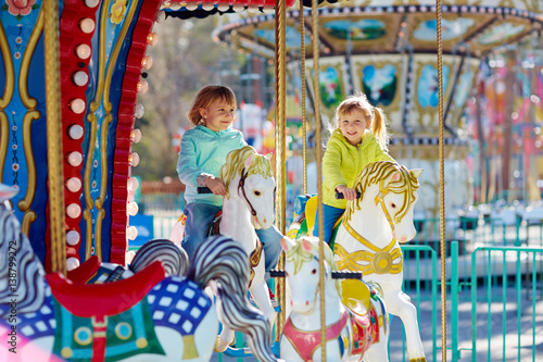 Fotografie, Obraz  Cute little sisters enjoying spring in funfair: they riding on colorful carousel