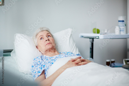 Lonely senior woman lying thoughtful on white sheets in hospital ward Wallpaper Mural