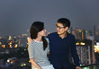 Asian Couple looking each other on rooftop with city background, Bangkok, Thailand