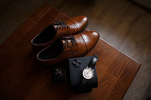 Wedding Accessories For Groom: Brown Shoes, Cufflinks, Hand Watch And Wedding Rings On Wooden Table