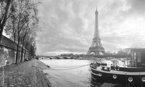Poster Paris Beautiful panoramic view of the Eiffel Tower and Jena bridge from the river Seine embankment. Dramatic cloudscape. Traditional citycape in backlit morning sunbeam. BW photography. Paris, France.