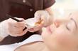Peeling chemiczny, zabieg złuszczający. Kosmetyczka nakłada na twarz kobiety preparat kosmetyczny.
