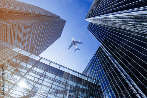 Airplane flying over business skyscrapers. Canvas Print