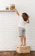 Cute Little Boy Reaching For The Cookies On The Kitchen Shelf