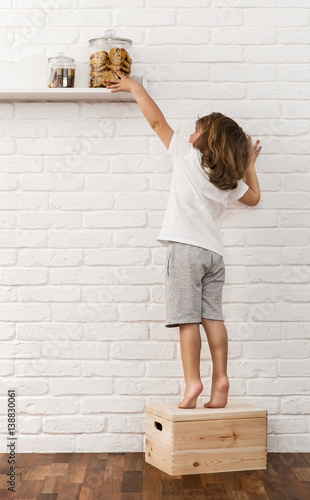 Photo Cute little boy reaching for the cookies on the kitchen shelf