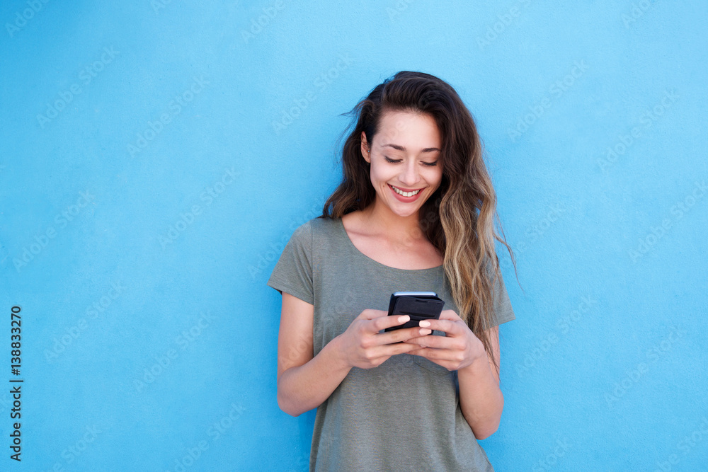 Fototapety, obrazy: young smiling woman using mobile phone against blue background