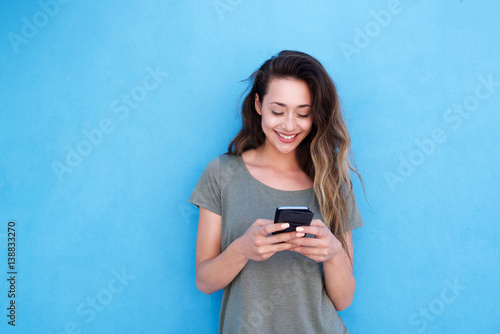 young smiling woman using mobile phone against blue background Fototapeta