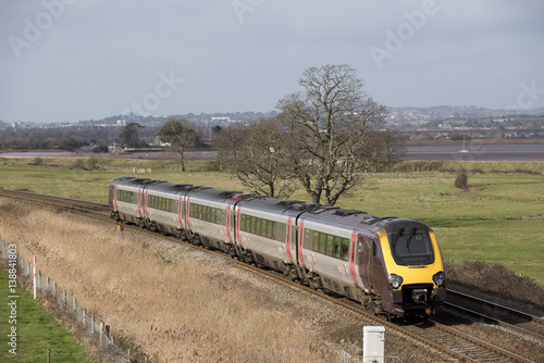 Fotomural  A Virgin Trains company passenger train passing through English countryside sout