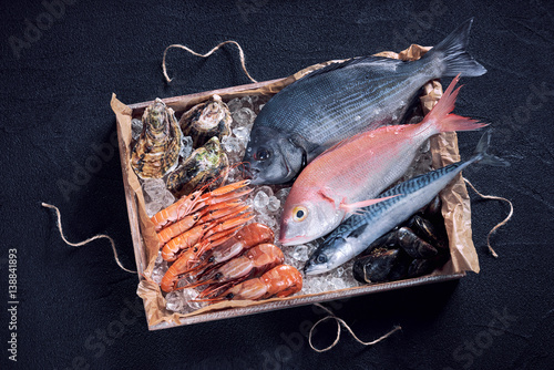 Poster Fish Fresh spanish fish and seafood in wooden box on black stone table