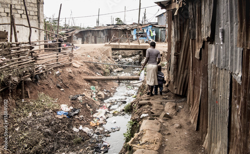 People walking along an open sewer in a slum in Africa