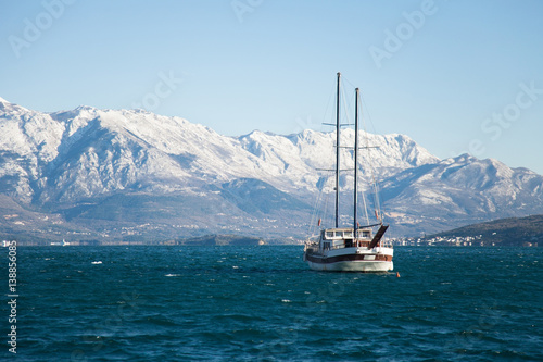 Foto op Plexiglas Caraïben Yacht is sailing in cold winter sea near snow mountains.