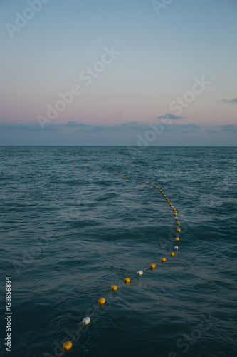 Fishing floats on sea surface at sunset