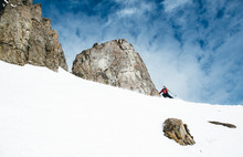 Skier Descending Snowy Slope By Rock Formations