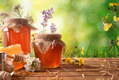 Two honey pots with green nature background with flowers