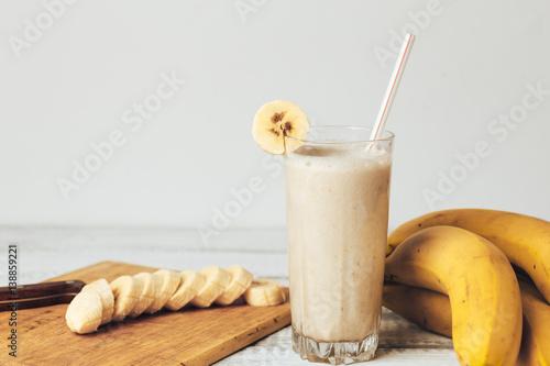 Leinwand Poster Fresh homemade banana smoothie, cutting board and bananas on white rustic wood