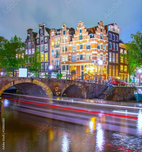 kanal-w-amsterdamie-i-smugi-swiatel-przeplywajacego-statku-pod-mostem