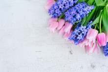 Pink Tulips And Blue Hyacinths Flowers On White Wooden Table