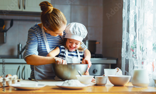 Poster Cuisine happy family in kitchen. mother and child preparing dough, bake cookies