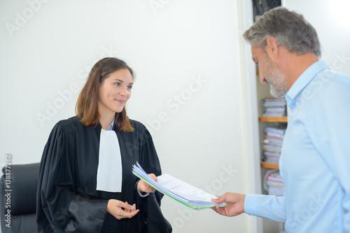 Fotografija  Man passing paperwork to legal worker wearing robes