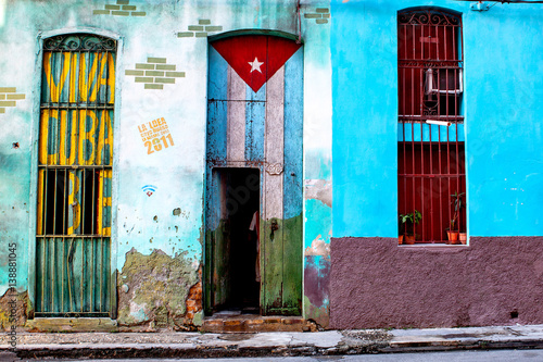 "Old shabby house in Central Havana painted with the Cuban flag and a ""Viva Cuba"" Libre writing"