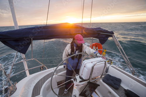 Fotomural Man Standing At Helm Of Yacht Sailing In Sea During Sunset