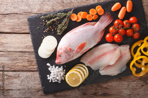 Poisson Raw fresh whole red tilapia, fillets and vegetables, spices close-up on a cutting board. Horizontal top view