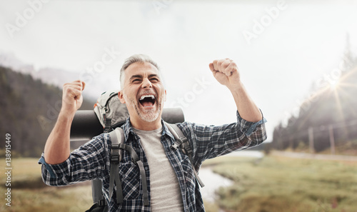 Stampa su Tela  Cheerful hiker celebrating with raised fists