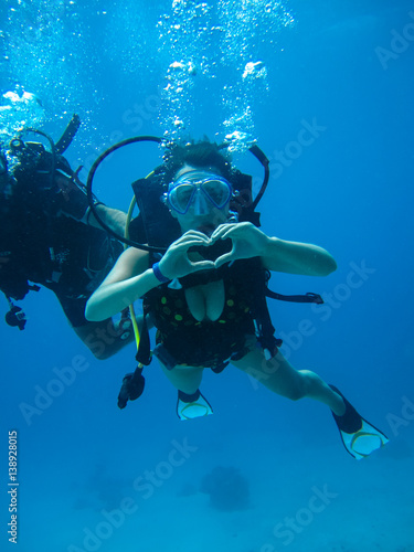 Poster Duiken Underwater shoot of a young female diving and showing love signal