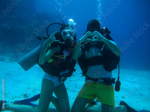 Staande foto Duiken Young couple on the seafloor show different gestures while diving