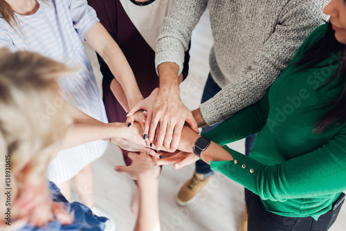 Fotografía  High angle shot of a group of colleagues standing in a circle with their hands i