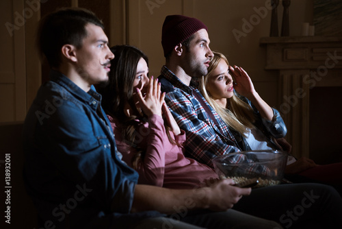 Fotografie, Obraz  side view of scared friends watching movie with popcorn at home