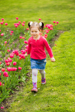 Cute Funny Active Girl Of Four Years Old Running Alone Cheerfully Outside Along Flowerbed With Pink Tulips In Spring Sunny City Park. Vertical Color Photography.