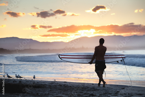 Foto Surfer walking on the shore along the beach lokking at the stunning sunset in Byron Bay, NSW, Australia