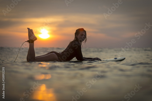 Foto op Canvas Bali Indonesia, Bali, female surfer in the ocean at sunset