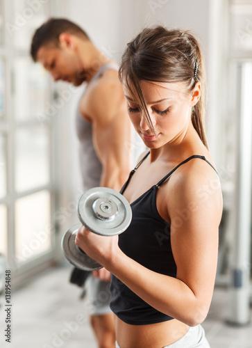 Plakat Młoda kobieta z sporta ciałem robi treningowi przy gym. Podnosić dumbbells.