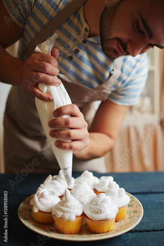 Portrait Of Male Chef Bending Over Kitchen Table Decorating Freshly Baked Golden Ins With White Cream