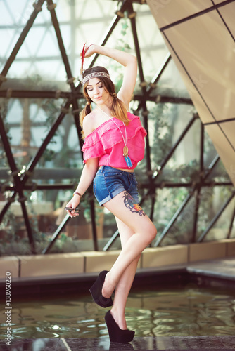 Modern American Native Indian Girl With Pink Blouse Denim Shorts And Red Feather
