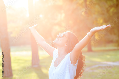 Beautiful young woman in park with her arms outstretched.