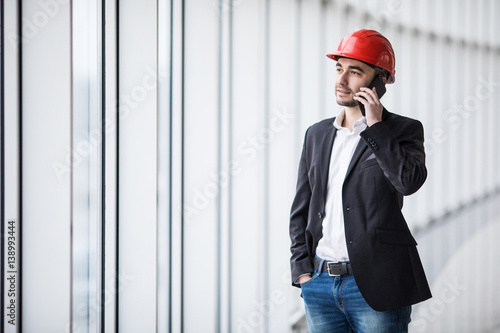 Portrait of an engineer talking on the phone against panoramic windows