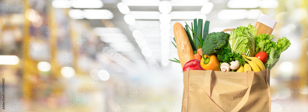Fototapeta Eco friendly reusable shopping bag filled with vegetables on a blur background