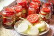 Canning of fresh tomatoes with onions for winter in jelly marinade. A shot of onion rings and red ripe sliced tomato on plate, being put in a jar for winter
