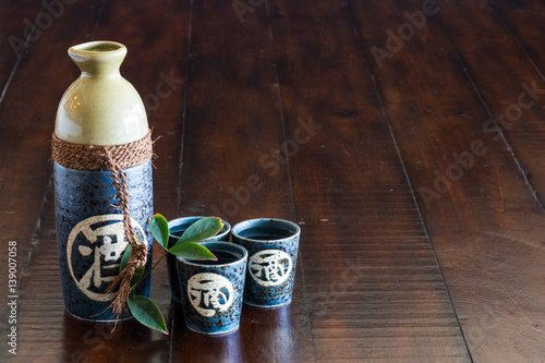 A bottle of sake and three sake cups on the rustic wood table.