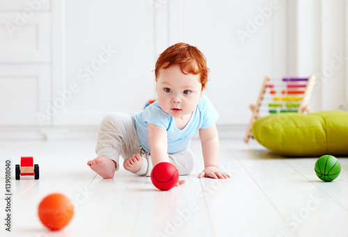 Photo  cute infant baby crawling on the floor at home, playing with colorful balls