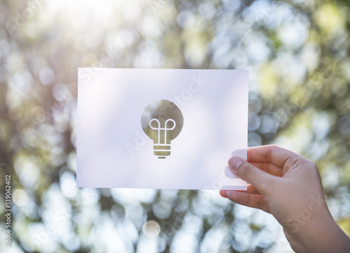 Valokuva  Human hand holding light bulb perforated paper craft in nature