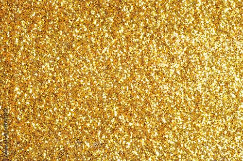 Obraz Sprinkle glitter gold dust on a black background with copy space - fototapety do salonu