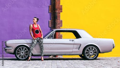 Fotografie, Obraz  Jeune femme debout devant une voiture Américaine
