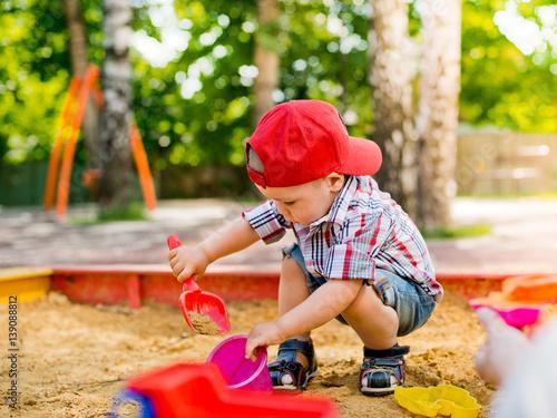 Fotografie, Obraz  child plays with sand